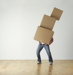 Hiring movers and their skills at packing, man holding boxes