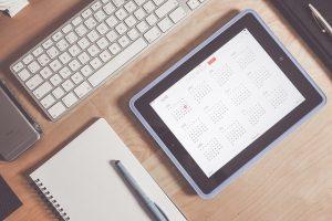 A calendar on a tablet next to a keyboard.