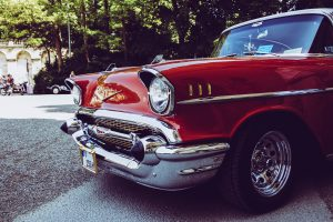 There is a red classic car parked in the street.