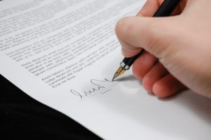 There is a person signing an important document, because gathering all the documents is a crucial step while transporting your classic car from SA to the US.