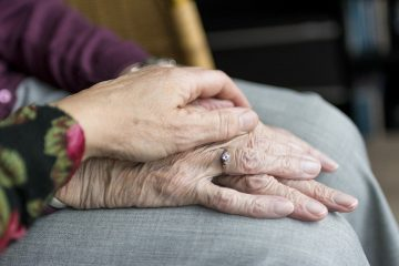 A daughter holding a hand of her elderly mother.