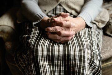 An elderly woman sitting and holding her hands on the lap.
