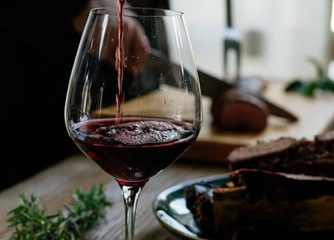 A glass of red wine placed on a table.