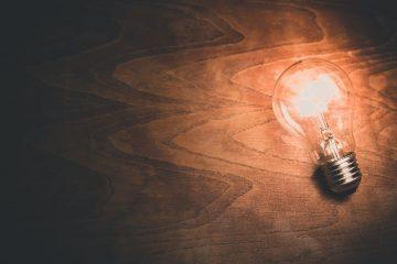 A light bulb on a wooden surface