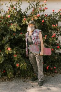 A elderly man with a beard standing in the sun with a skateboard