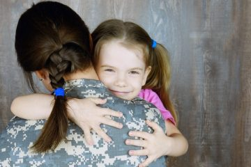 A woman in a military uniform hugging her little daughter.