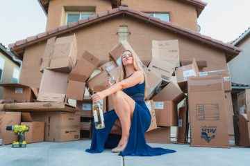 A woman with a glass of champagne in front of a huge pile of moving boxes after preparing household items for interstate relocation
